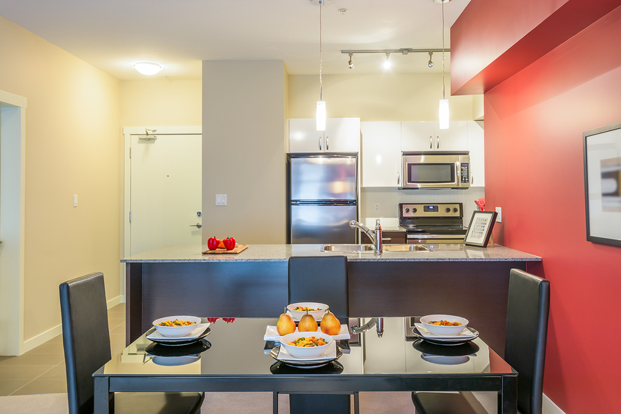 Modern red dining room with kitchen in a luxury apartment. Inter